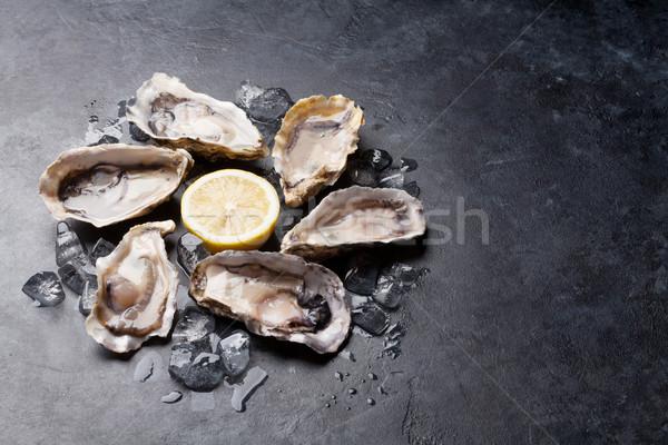 Opened oysters and lemon Stock photo © karandaev