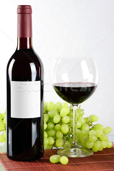 Bottle and glass of red wine and grapes in back Stock photo © karandaev