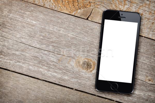 Smart phone on wooden table Stock photo © karandaev