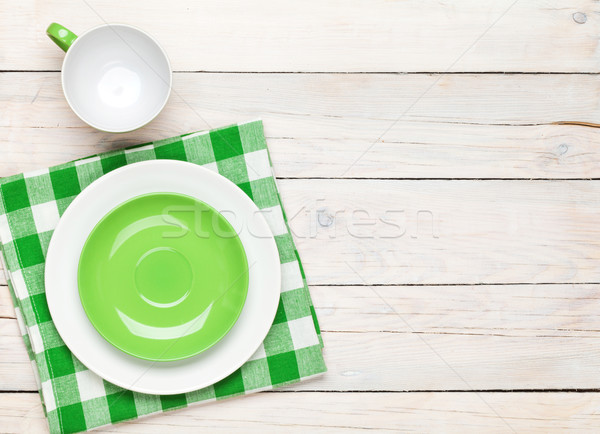 Empty plate, cup and towel over wooden table background Stock photo © karandaev