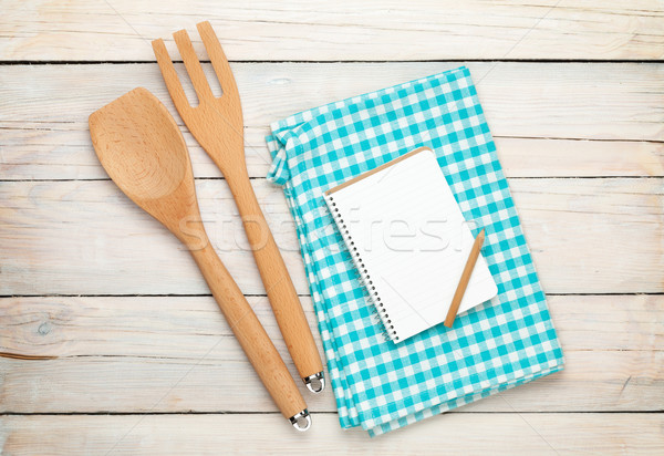 Kitchen utensil and notepad over wooden table Stock photo © karandaev