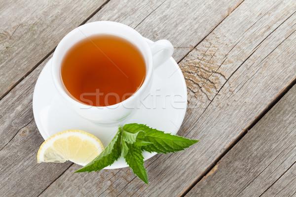 Green tea with lemon and mint on wooden table Stock photo © karandaev