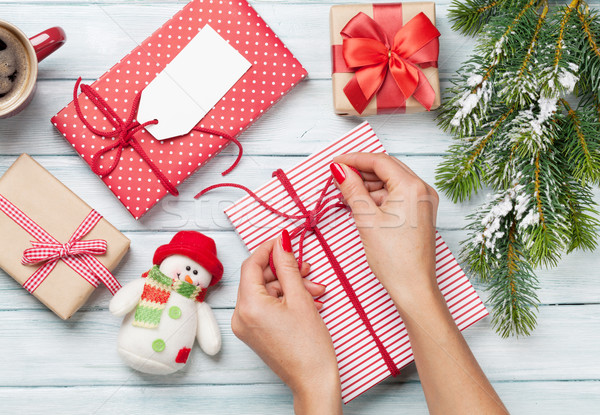 Female hands wrapping christmas gift Stock photo © karandaev