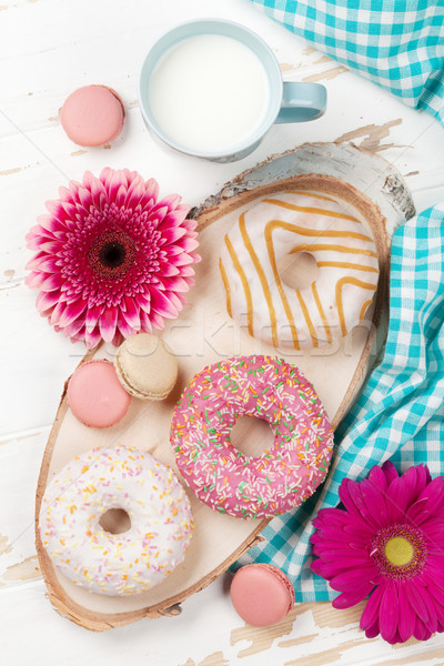 Milk, donuts and flowers on wooden table Stock photo © karandaev