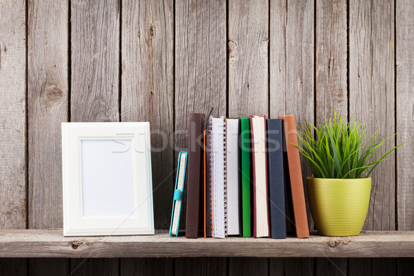 Wooden shelf with photo frames, books and plant Stock photo © karandaev