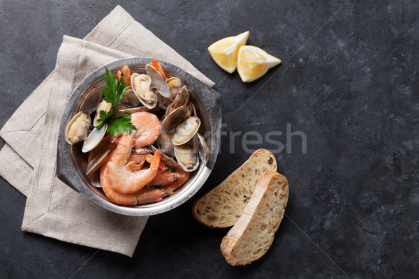 Fresh seafood bowl on stone table. Scallops and shrimps Stock photo © karandaev