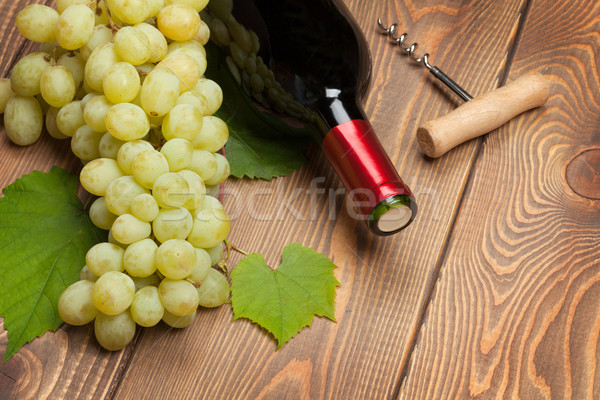 Red wine bottle and bunch of white grapes Stock photo © karandaev