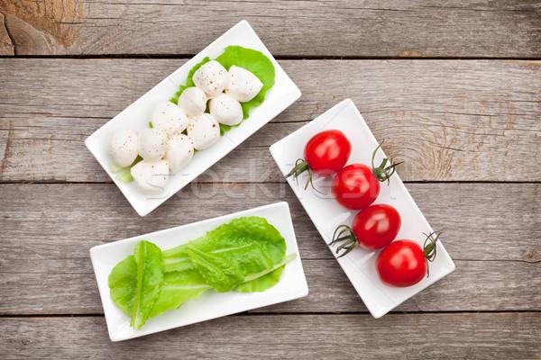 Tomaten mozzarella groene salade bladeren houten tafel Stockfoto © karandaev