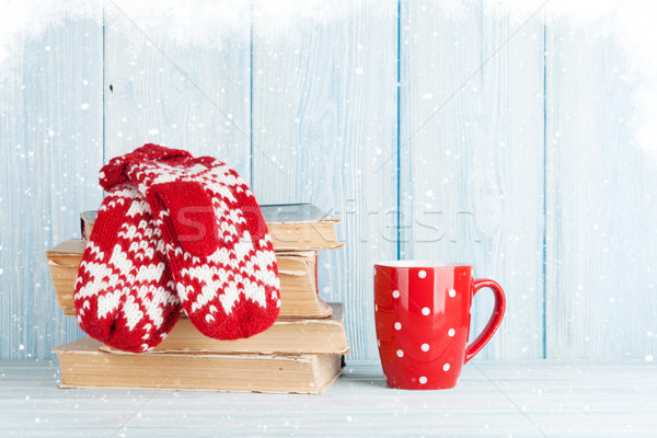 Hot chocolate cup and mittens over books Stock photo © karandaev