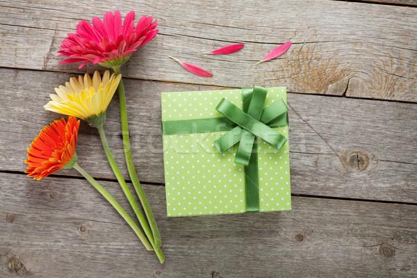 Three colorful gerbera flowers with gift box Stock photo © karandaev