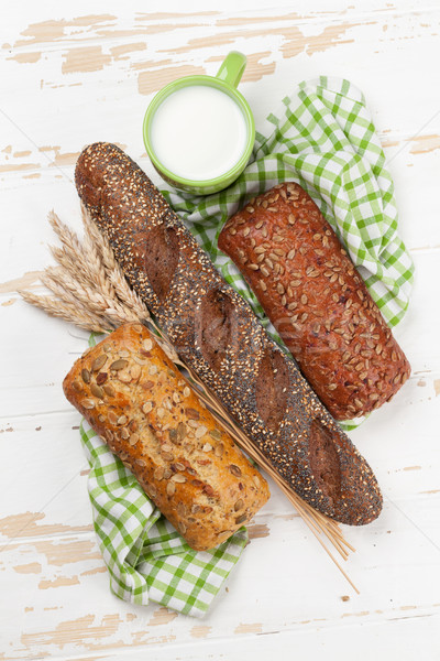 Various crusty bread and buns and cup of milk Stock photo © karandaev