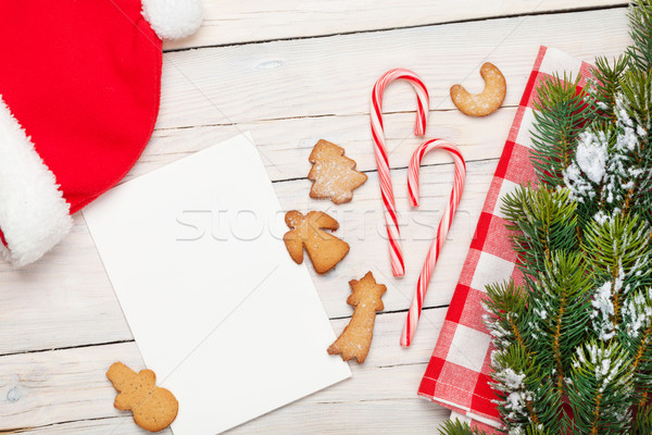 Christmas greeting card, santa hat, gingerbread cookies and snow Stock photo © karandaev