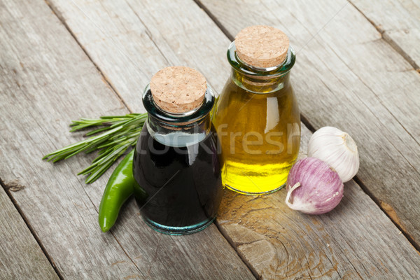 Olívaolaj ecet üvegek fűszer fa asztal fa Stock fotó © karandaev