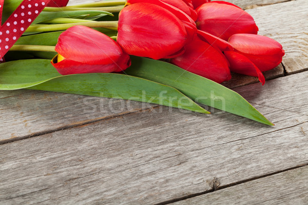 Fresh red tulips bouquet over wooden table background Stock photo © karandaev