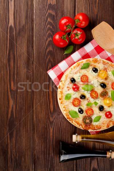 Italian pizza with cheese, tomatoes, olives and basil Stock photo © karandaev