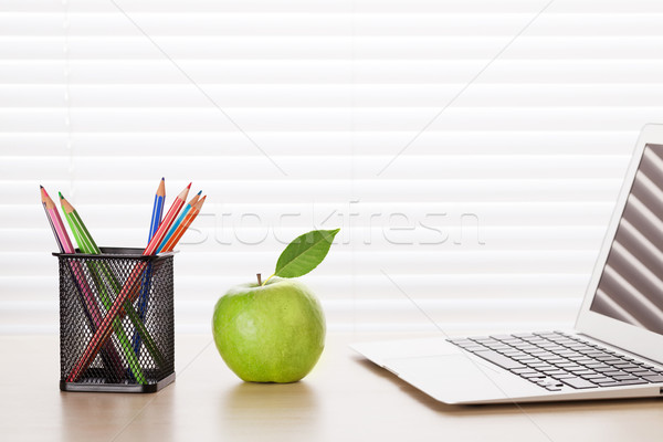 Office workplace with laptop, apple and pencils Stock photo © karandaev