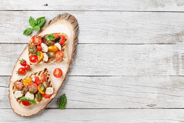 Bruschetta paradicsomok mozzarella bazsalikom koktélparadicsom fa deszka Stock fotó © karandaev