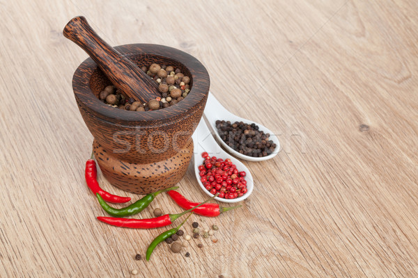 Mortar and pestle with red hot chili pepper and peppercorn Stock photo © karandaev