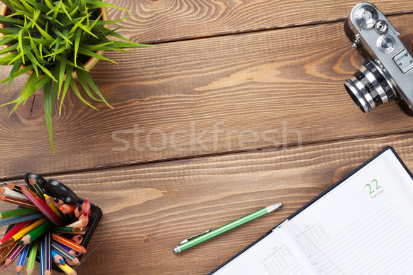 Office desk table with camera, supplies and flower Stock photo © karandaev