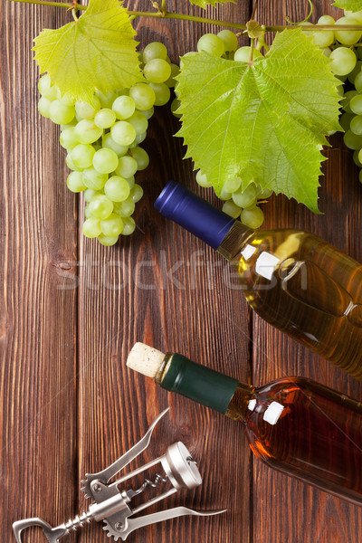Bunch of grapes, white wine bottles and corkscrew Stock photo © karandaev