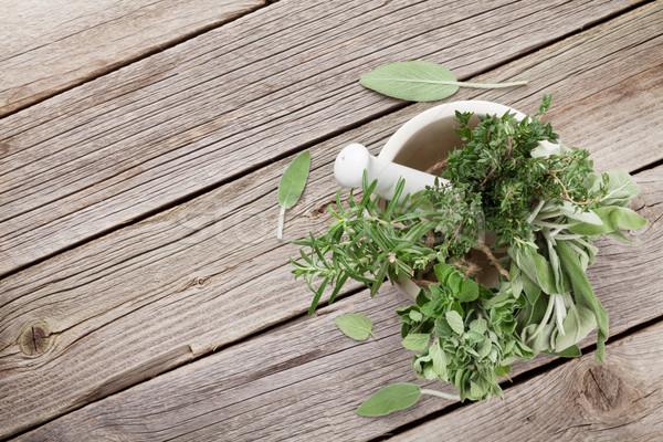 Fresh garden herbs in mortar on wooden table Stock photo © karandaev