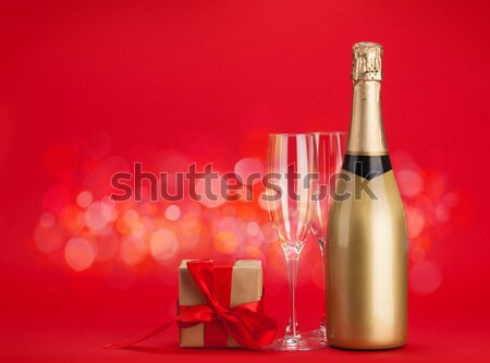 Champagne bottle, two glasses, letter and red rose flowers Stock photo © karandaev