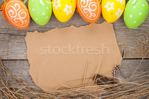 Easter eggs and paper for your greetings on wooden background Stock photo © karandaev