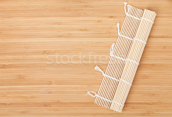 Sushi mat over bamboo table Stock photo © karandaev