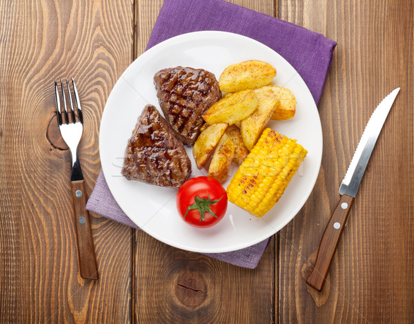 Steak with grilled potato, corn and salad on wooden table Stock photo © karandaev