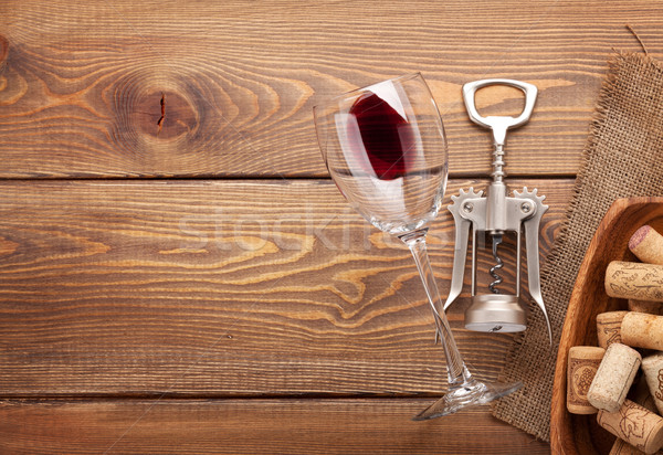 Red wine glass, corkscrew and bowl with corks Stock photo © karandaev