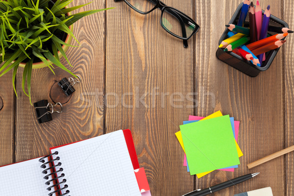Office table with flower, blank notepad and colorful pencils Stock photo © karandaev