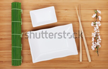Empty plates, chopsticks and sakura branch Stock photo © karandaev