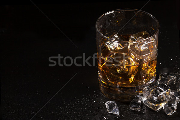 Glass of whiskey with ice on black stone table Stock photo © karandaev
