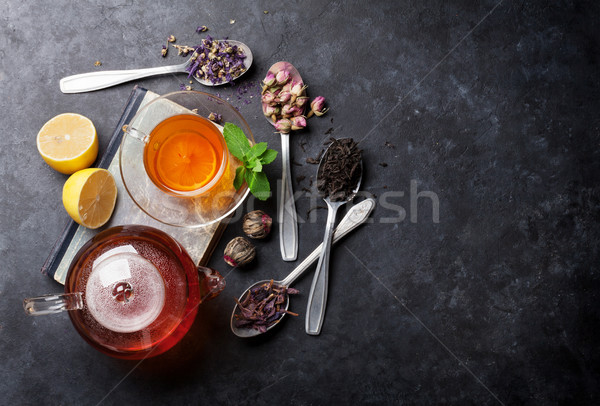 Tea cup, teapot and assortment of dry tea in spoons Stock photo © karandaev