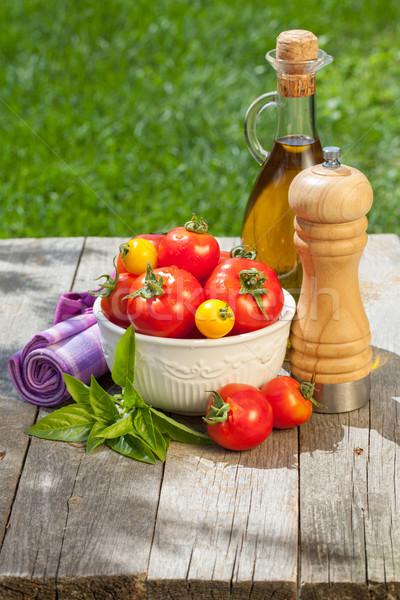 Fresh ripe tomatoes, olive oil bottle, pepper shaker and herbs Stock photo © karandaev