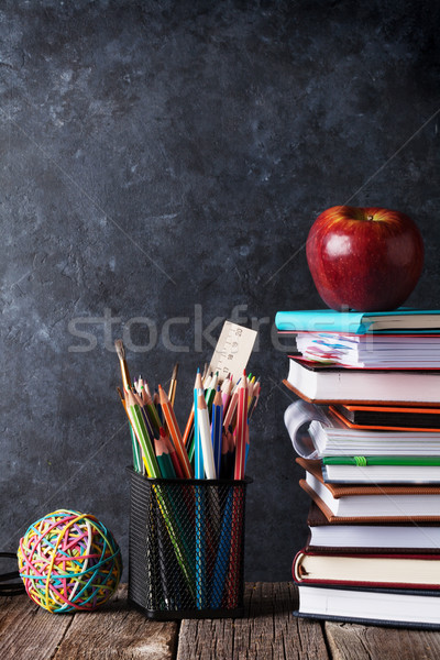 Notepads, supplies and apple in front of chalk board Stock photo © karandaev