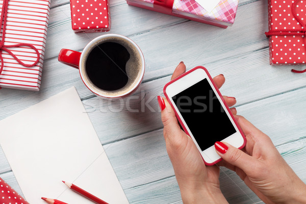 Female holding smartphone and wrapping christmas gifts Stock photo © karandaev