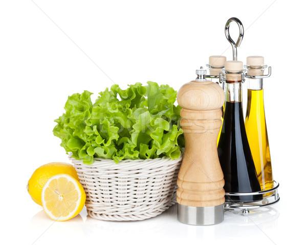 Lettuce in basket with lemon fruits, pepper shaker, olive oil an Stock photo © karandaev