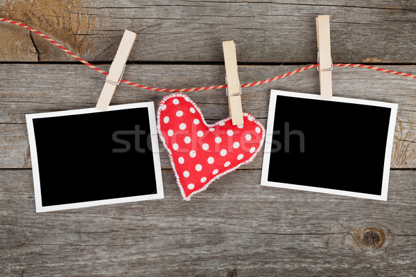 Two blank instant photos and red heart hanging on the clotheslin Stock photo © karandaev