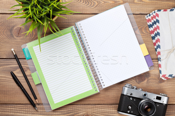 Office desk with calendar notepad, camera, supplies and flower Stock photo © karandaev