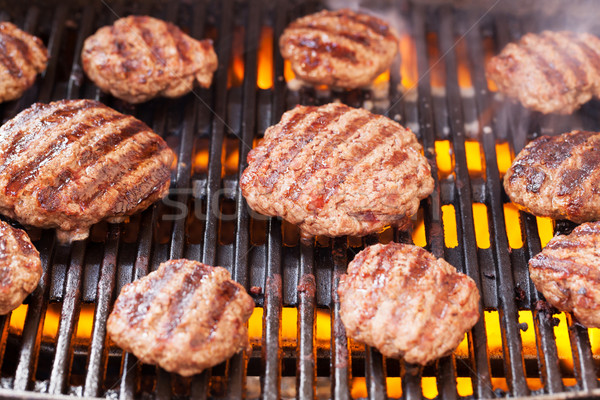 Burgers cooking on grill Stock photo © karandaev