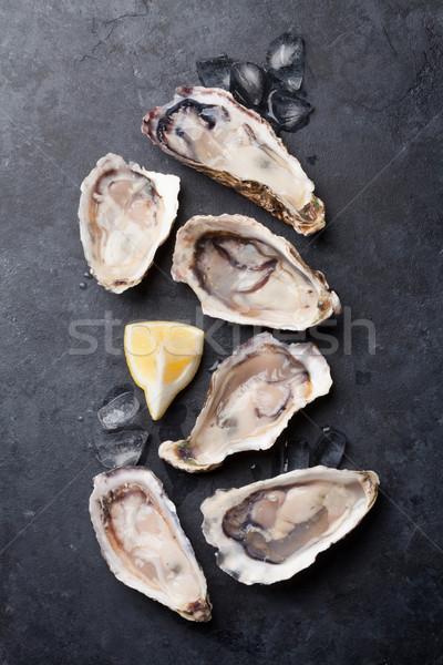 Oysters and lemon over ice Stock photo © karandaev