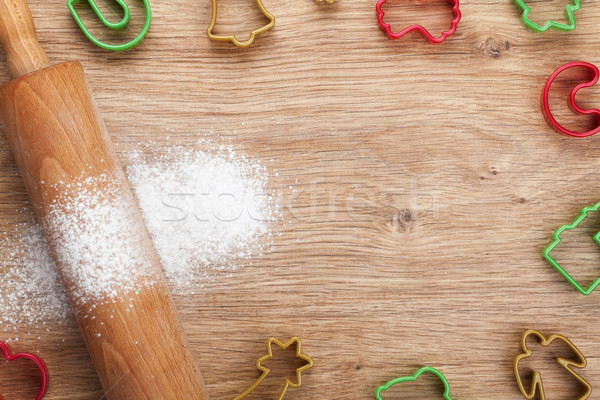 Rolling pin with flour and cookie cutters on wooden table Stock photo © karandaev