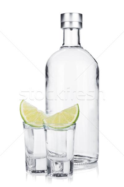 Bottle of vodka and shot glasses with lime slice Stock photo © karandaev