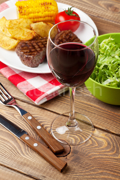 Glass of red wine, steak with grilled potato, corn and salad Stock photo © karandaev