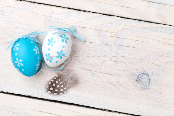 Easter background with blue and white eggs and feather Stock photo © karandaev