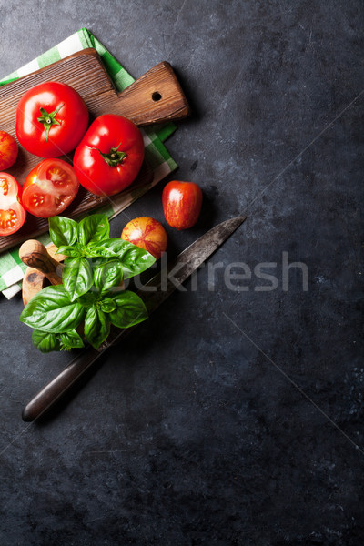 Fresh ripe garden tomatoes and basil on stone table Stock photo © karandaev