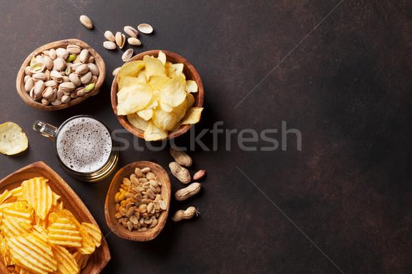 Lager beer and snacks on stone table Stock photo © karandaev