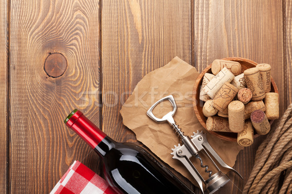 Stock photo: Red wine bottle, corks and corkscrew over wooden table backgroun