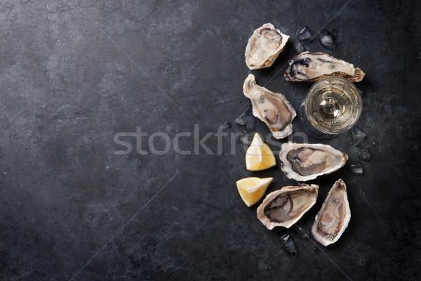 Oysters with lemon and white wine Stock photo © karandaev